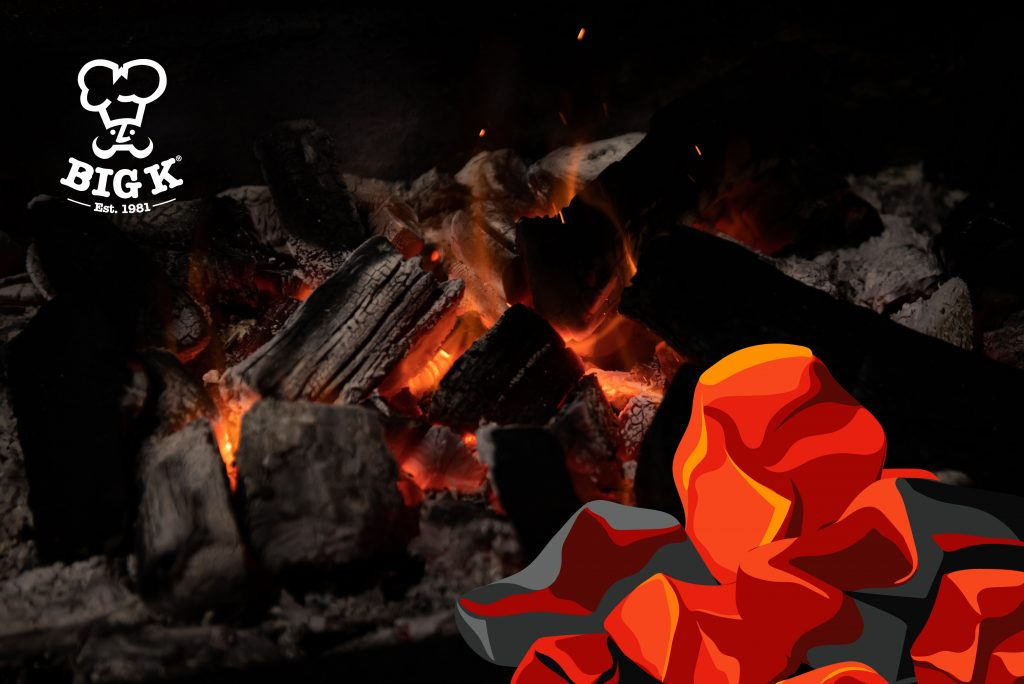 a pile of lumpwood charcoal lies burning in a barbecue grill glowing red-hot.