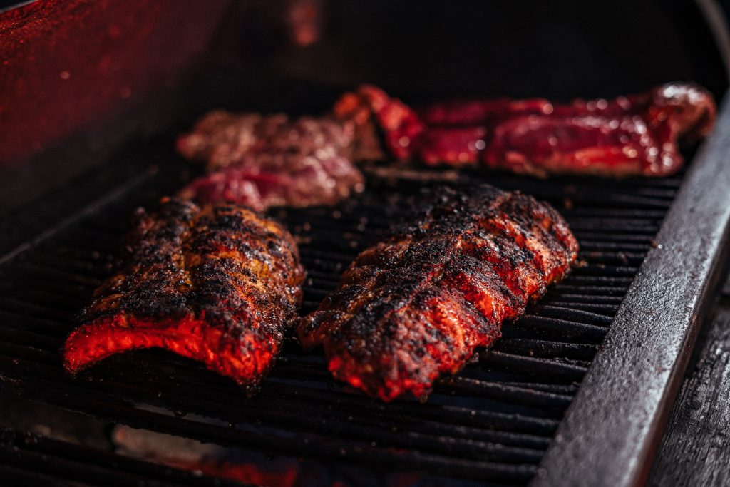 Cooked beef and pork shoulder lie perfectly crispy on a BBQ smoker grill base