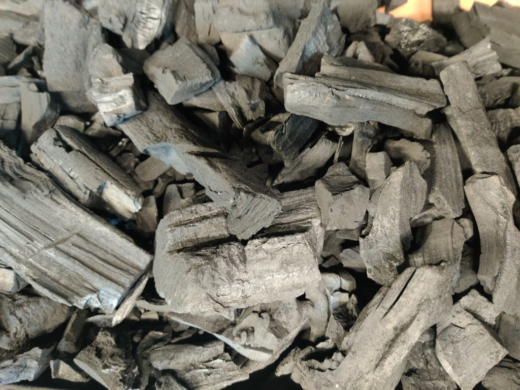 Big K professional lumpwood charcoal burns in a barbecue smouldering red hot