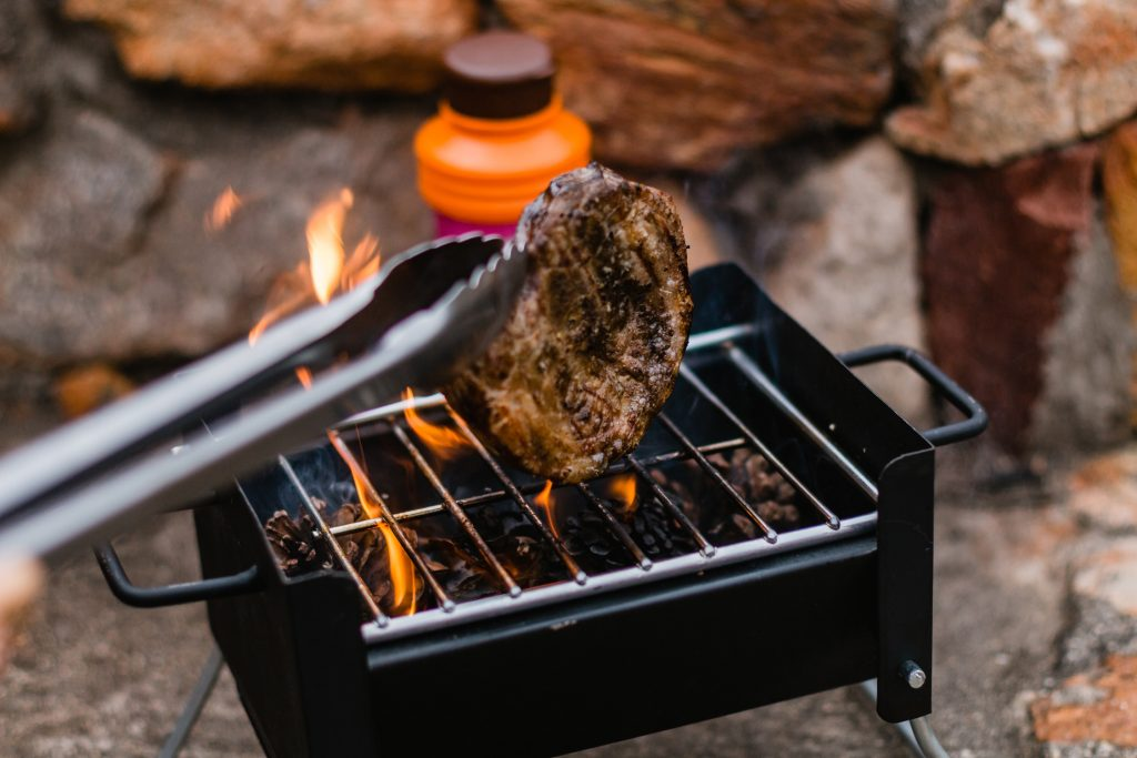 Charcoal within a small micro BBQ grill is burning with orange flames as a steak is turned