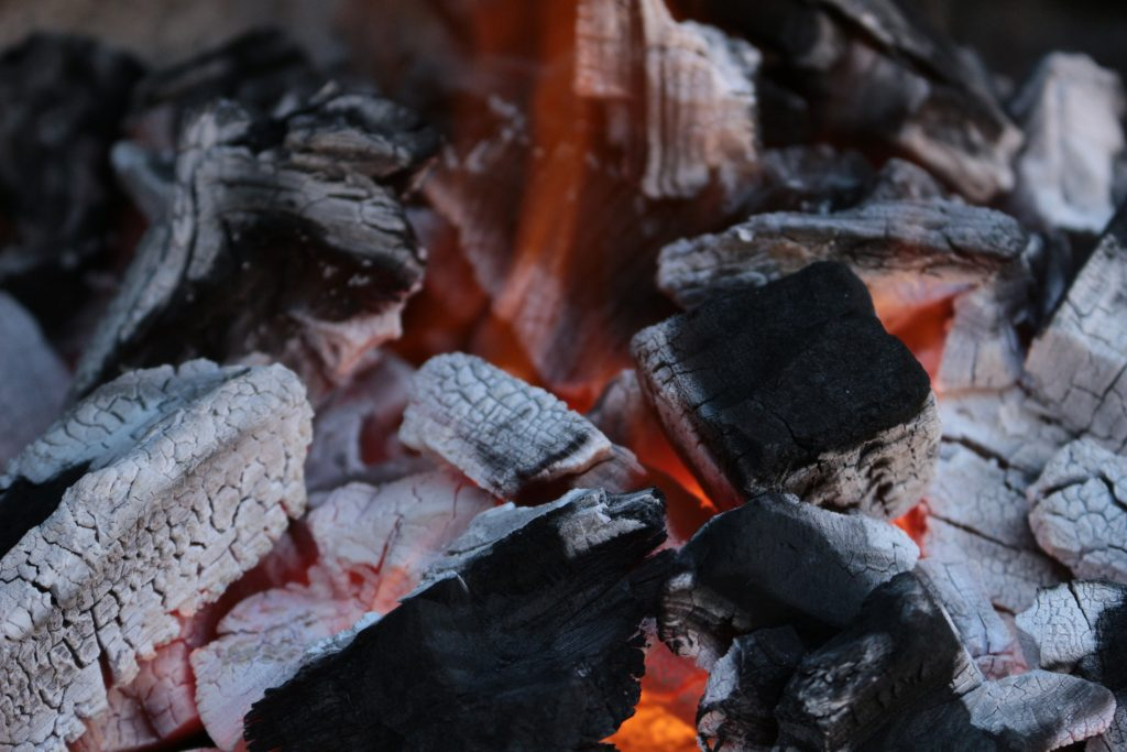 Big K Home Lumpwood Charcoal burns on a grill base with white ash and red glow