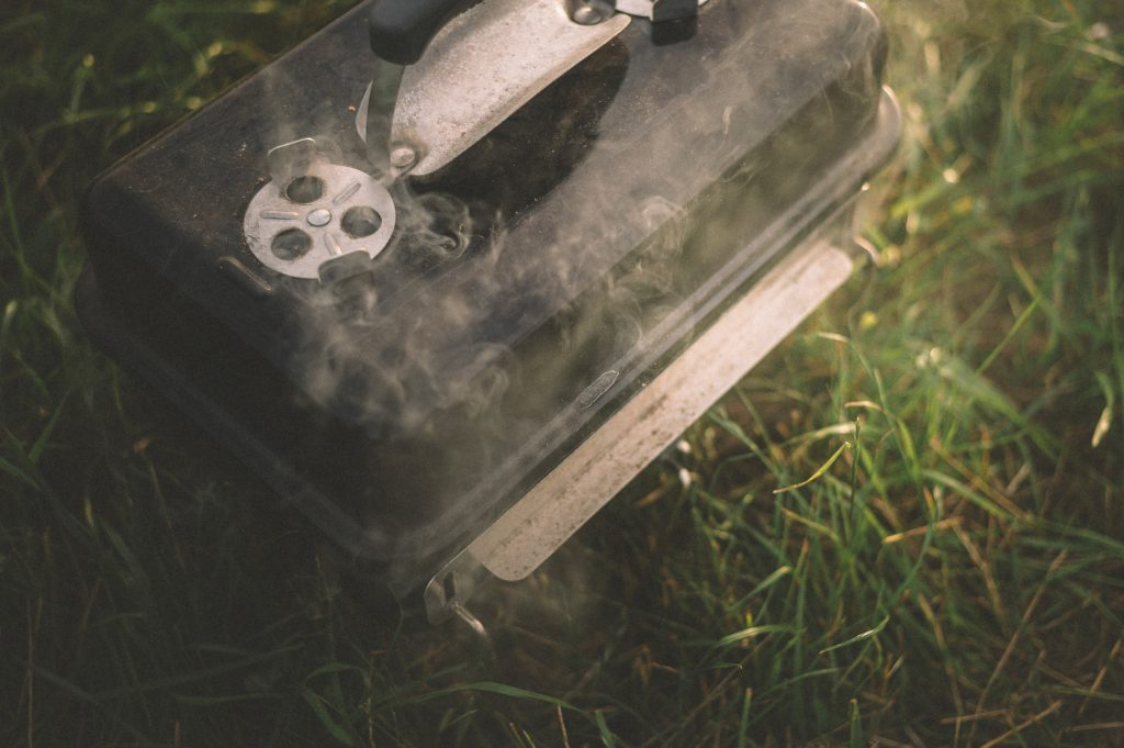 A square closed lid BBQ grill emits smoke as it is positioned on the green grass