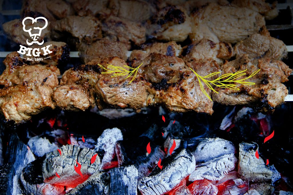 Succulent steaks lie cooking on a grill with heat coming form a pile of smokeless fuel underneath the grill gate.