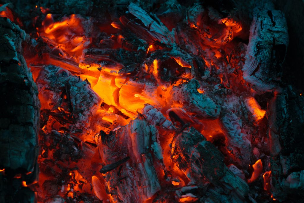 A smokeless fuel of burning charcoal glows with red and orange embers in a grill base.
