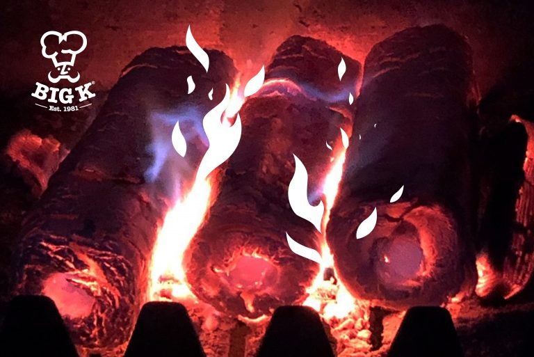 Several fire logs burn red hot in a fireplace